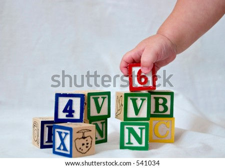 a baby's hand picking up a block