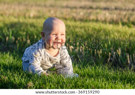 A baby sitting on lawn enjoying the sunset - stock photo