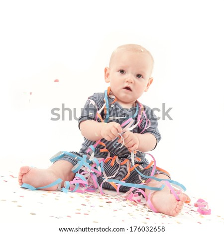A baby sitting wrapped in various paper ribbons. - stock photo