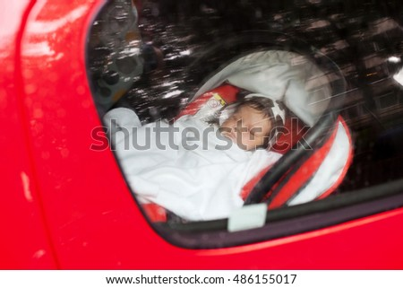 A baby sleeping in a special car seat.