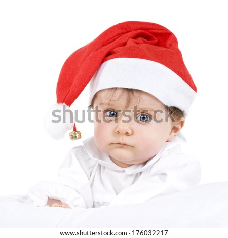 A baby wearing a Santa hat with a bell on it.