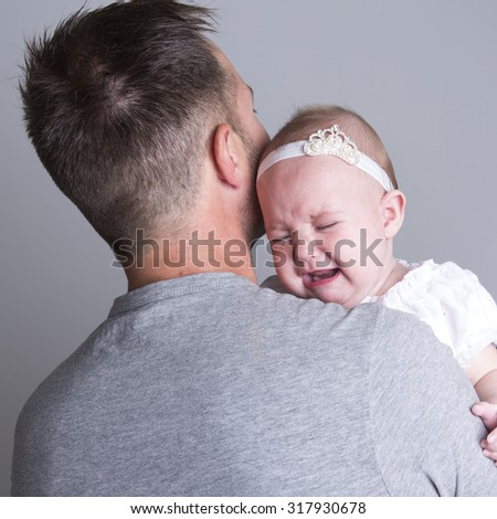A baby who cry on the hand of is father - stock photo