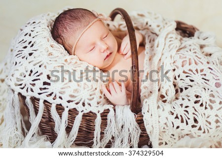 A baby who sleeps in a basket portrait - stock photo