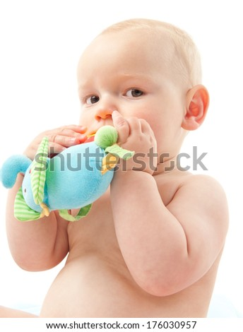 A baby with a soft toy in the hands being held to the mouth.