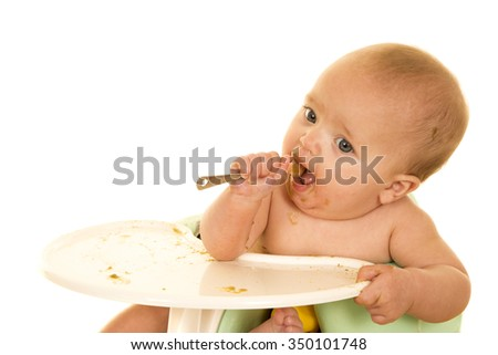 A baby with her spoon in her mouth feeding herself. - stock photo