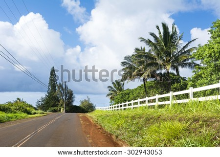 A back country road in a remote part of Kauai, Hawaii with beautiful green grass and a white fence lining the roadway.