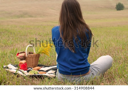 A back view of young girl sitting on a grass and enjoying autumn landscape, a picnic basket with flowers and fresh pastry and a bright red cup of hot coffee are placed on a blanket nearby - stock photo