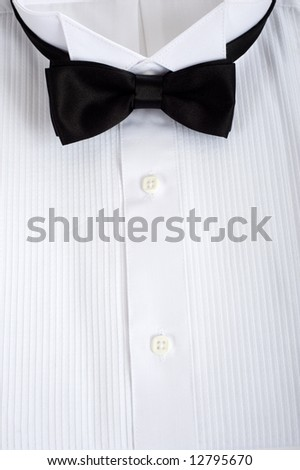A backgound consisting of a tuxedo shirt with a black silk tie with copy space, formal attire for wedding or waiter or service personell