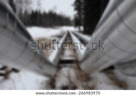 A background blur of an above ground oil and gas pipeline in a winter landscape - stock photo