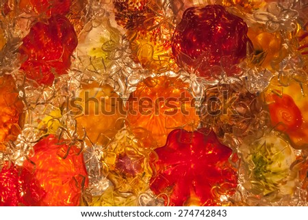 A background image of red, orange, and clear blown glass