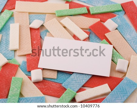 A background of various sticks and pieces of gum support a blank white business card. - stock photo