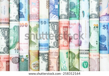 A backgrounds with colorful of many roll currency from many country - stock photo