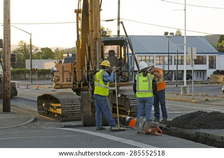 A backhoe, tracked excavator and crew dig a utility trench for water and other utilities at a new commercial road development