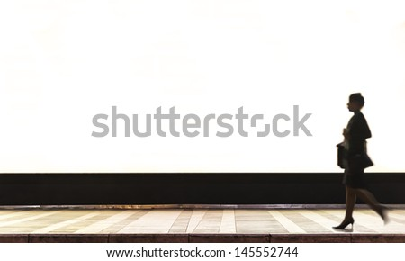A backlit poster advertising in a terminal station. The slow time in the photo shoot has allowed us to make the ethereal person. - stock photo