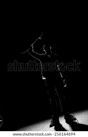 A backlit skateboarder guy holding up his skateboard deck under dramatic rim lighting. - stock photo