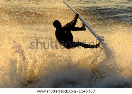A backlit surfer catches air against the warm colors of the setting sun.