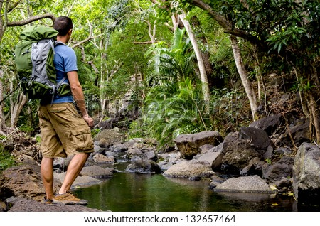 A backpacker in jungle next to river in Hawaii. - stock photo