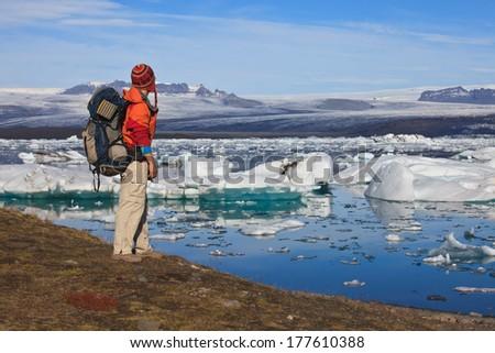 A backpacker overlooking Jokulsarlon Lagoon and Vatnajokull Glacier  , Iceland - stock photo