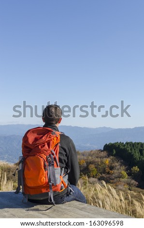 A backpacker relaxes and enjoys the mountain view with copy space. - stock photo