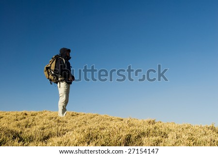 A backpacker walk on a yellow grassland in mountain.