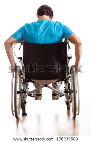 A backside of a man driving a wheelchair - stock photo