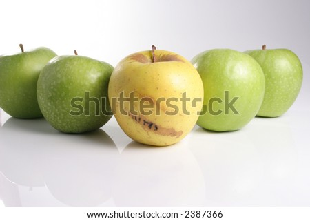 A bad green apple beside a bundle of healthy ones - stock photo
