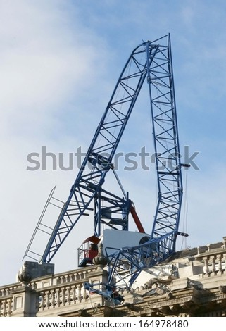 A badly damaged crane caused by strong winds, on the roof of a building. - stock photo