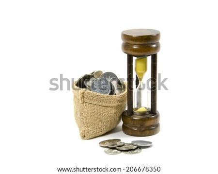 a bag full of coins and sand glass - stock photo