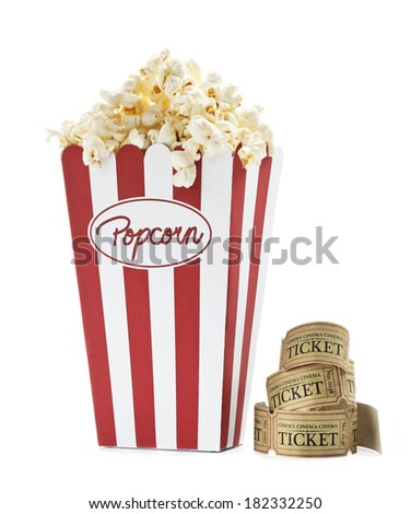 a bag full of popcorn and some old cinema tickets with white background - stock photo