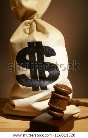 A bag of money and gavel represent many legal expenses. - stock photo