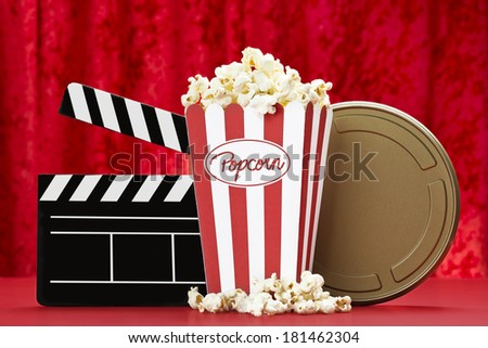 a bag of popcorn, black cinema clapper board and a golden film can with red background - stock photo