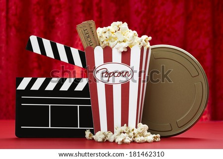 a bag of popcorn, clapper board, film can  and cinema tickets with red background - stock photo