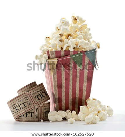 a bag of popcorn, little flags and cinema tickets with white background - stock photo