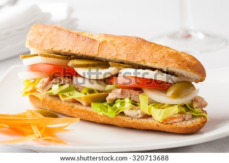 A baguette sandwich with tuna fish, onion, tomato, pickles, olives, boiled egg and lettuce
