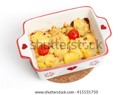 A baked potatoes with cheese and tomatoes in casserole dish - stock photo