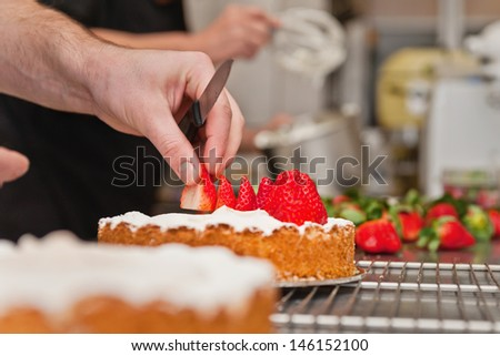 a baker puts the finishing touches on a strawberry cake in a professional kitchen - stock photo