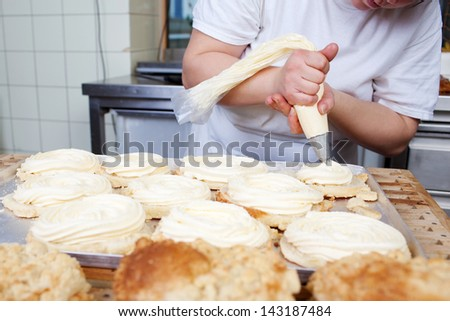 A baker while filling pastry with cream in bakery - stock photo