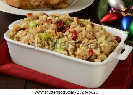 A baking pan of stuffing with cranberry and celery on a Christmas table - stock photo