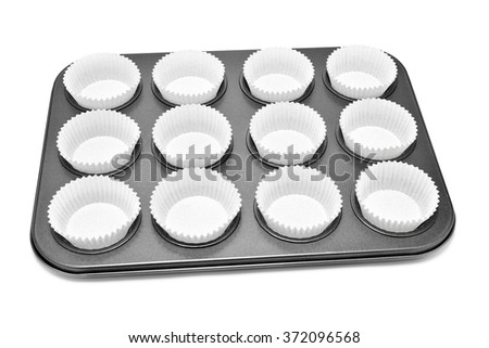 a baking tray with different holes for muffins or cupcakes, with some paper cups, on a white background - stock photo