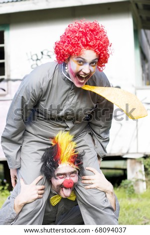 A Balancing Act Sees A Clown Riding On Another Clowns Back In A Playful Display Of Clowning Around - stock photo