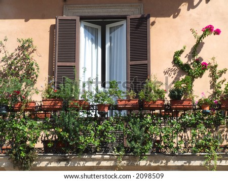 A balcony with flowers and a window with brown shutters - typical Mediterranean architecture.