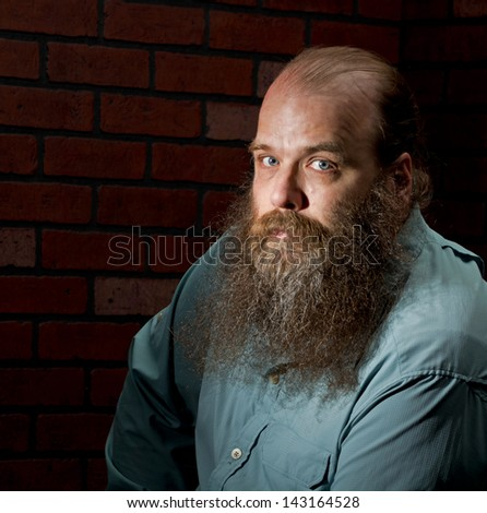 A balding middle aged man with a big bearded against a brick wall looks into the camera with his light blue eyes. - stock photo