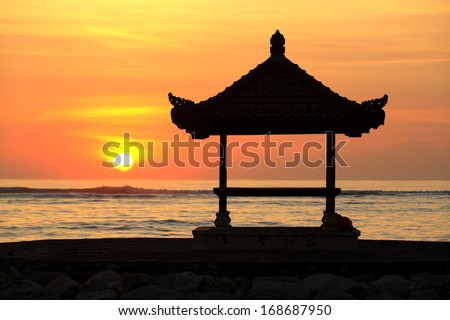 A Balinese Pagoda on the beach at Sanur. The sun is rising over the ocean. Bali, Indonesia - stock photo