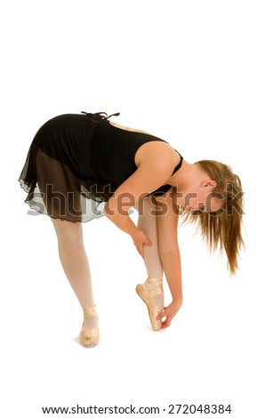 A Ballerina Stretches to Warm-up for Ballet Class - stock photo