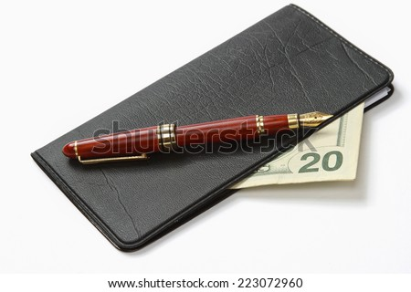 A ballpen on a closed leather checkbook - stock photo
