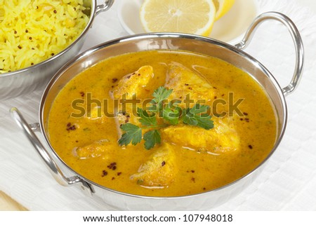 A balti dish with a Peshwari style chicken curry, with basmati rice and lemon in the background. - stock photo