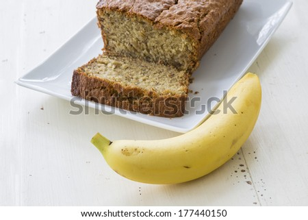 A banana and a platter with a loaf of homemade banana bread. - stock photo