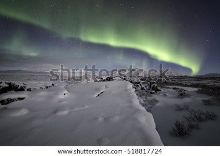 A band of bright northern lights blazing over a scene out of winter wonderland in Iceland, sparkling snow covered ground below leading into the image