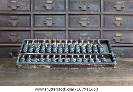 A bank's vintage abacus or counting frame laid in front of drawers of a vintage filing cabinet.