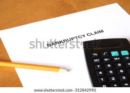 A bankruptcy claim form with a calculator and pencil. - stock photo